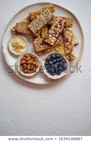 Mixed composition of energy nutrition bar, granola on ceramic plate over white background Stock photo © dash