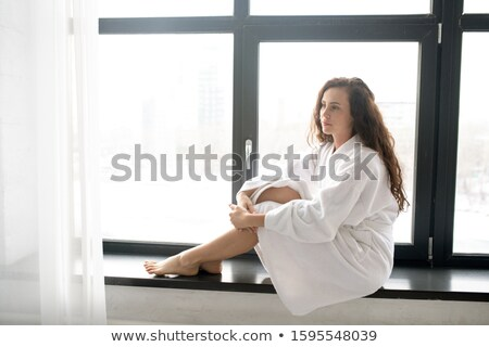 Young brunette serene woman in soft white bathrobe relaxing on windowsill Stock photo © pressmaster