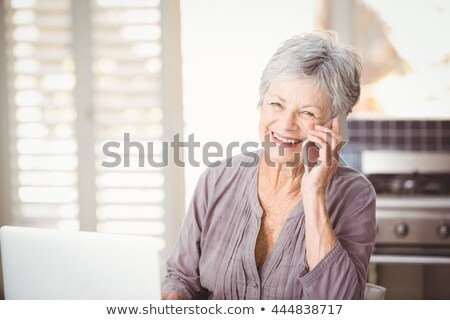 senior woman with hands on hips in kitchen Stock photo © dolgachov