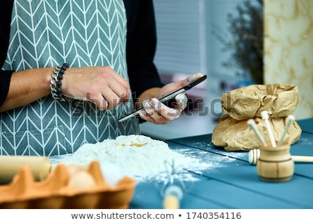 Man using electronic tablet pc in kitchen for baking.  Stock photo © Illia