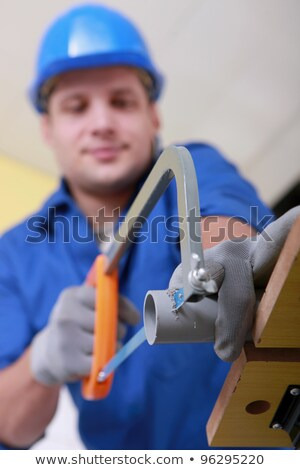 Plumber sawing grey plastic pipe Stock photo © photography33