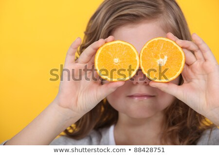 little girl covering eyes with slices of orange stock photo © photography33