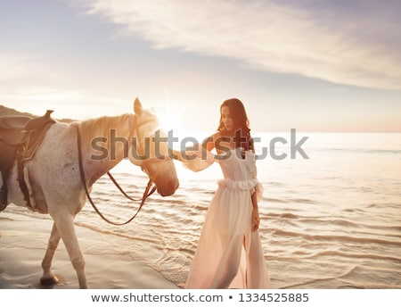 lovely woman in elegant dress on white sand stock photo © dolgachov