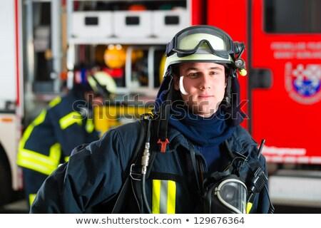 young fireman in uniform in front of firetruck stock photo © kzenon