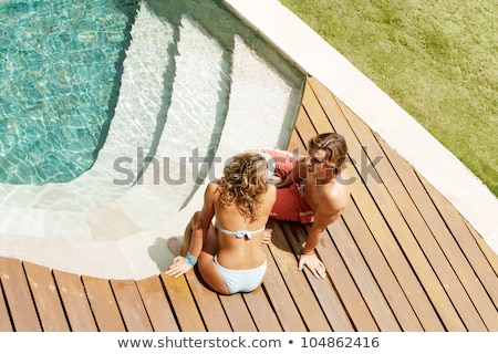 happy woman tanning in bikini over swimming pool Stock photo © dolgachov