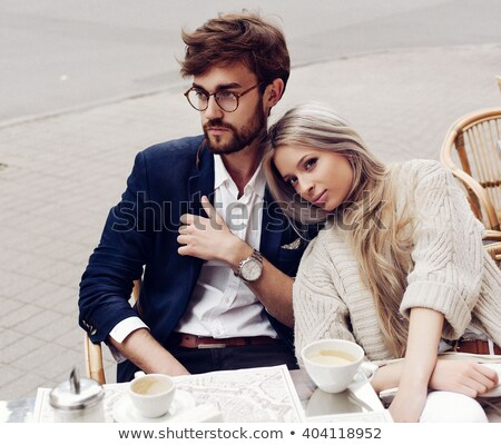 Smiling young loving couple sitting in cafe and eating. Stock photo © deandrobot