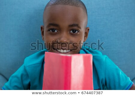 Close-up portrait of smiling boy with red novel at home Stock photo © wavebreak_media