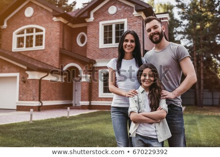 Family standing in front of their house Stock photo © IS2