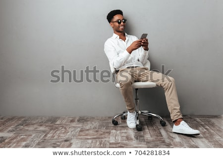 man with phone sitting in chair stock photo © is2