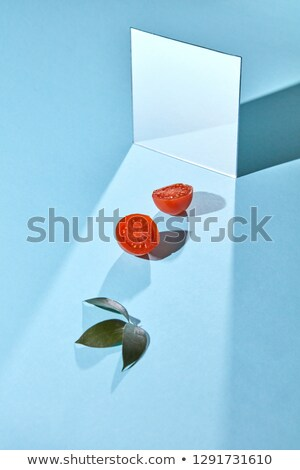 Halves of ripe tomatoes, green leaves and a mirror on a blue background with copy space. Food compos Stock photo © artjazz