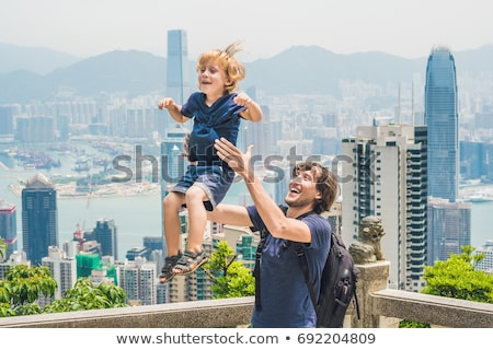 father and son travelers at the peak of victoria against the backdrop of hong kong traveling with c stock photo © galitskaya
