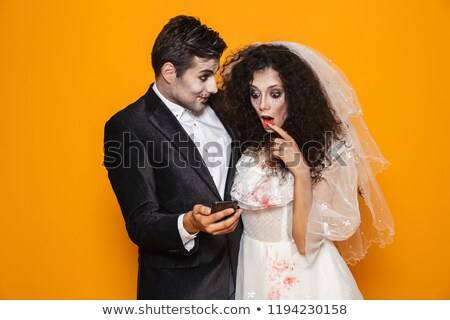 Photo of excited zombie couple bridegroom and bride wearing wedd Stock photo © deandrobot
