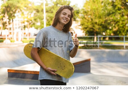 photo of youngster 16 18 in casual wear carrying skateboard in s stock photo © deandrobot