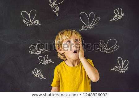 the boy is bitten by mosquitoes on a dark background on the bla stock photo © galitskaya