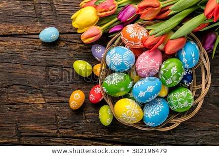 colored easter eggs in basket and tulip flowers stock photo © dolgachov