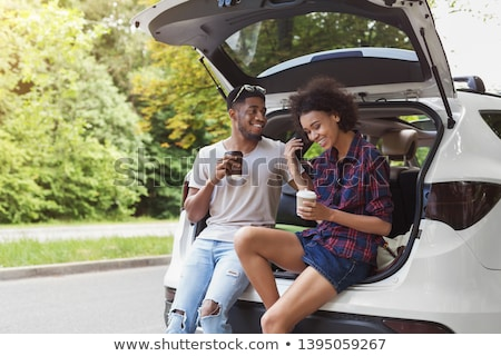 happy couple with coffee at hatchback car trunk Stock photo © dolgachov