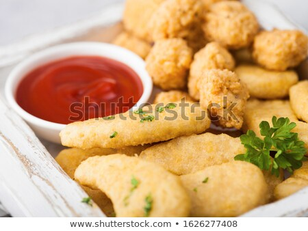 Buttered chicken nuggets and popcorn bites in white vintage wooden box with ketchup on light backgro Stock photo © DenisMArt