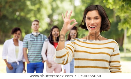 happy smiling woman in striped pullover showing ok Stock photo © dolgachov