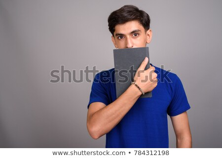 shy student boy hiding behind books Stock photo © dolgachov