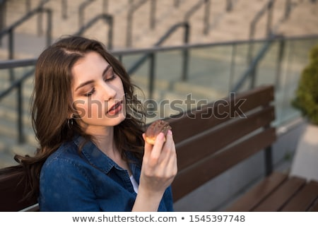 portrait of young pretty woman sitting on bench at summer or aut stock photo © hasloo