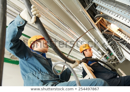 Two electrical workers installing fuse box Stock photo © photography33