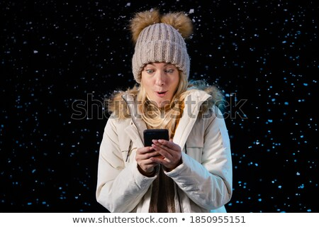 Attractive woman writing a text on her phone while standing against a white background stock photo © wavebreak_media