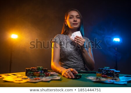 woman sitting at table of a casino holding chips in her hands stock photo © wavebreak_media