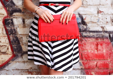 woman with clutch near wall Stock photo © chesterf