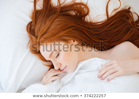pretty redhead woman with long hair lying in bed stock photo © deandrobot