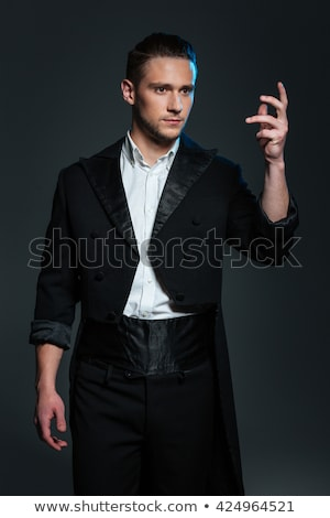 Serious young man magician in black tail coat showing tricks Stock photo © deandrobot