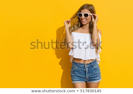 young blonde woman in short jeans posing on a white background Stock photo © traza