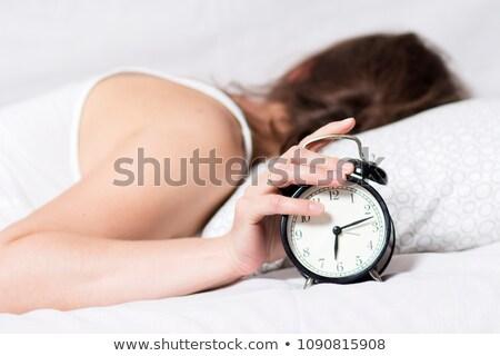 álmos · nő · ágy · kéz · ébresztőóra · fókusz - stock fotó © nobilior