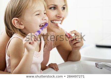 Nő fürdőszoba fogmosás mosolygó nő mosolyog boldog Stock fotó © monkey_business