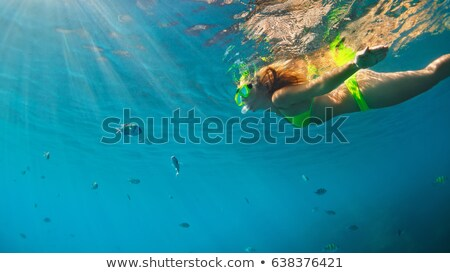 woman on beach with diving goggles looking over ocean stock photo © kzenon