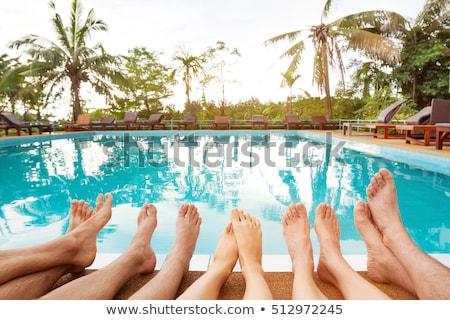 Friends sitting at swimming pool  Stock photo © Kzenon