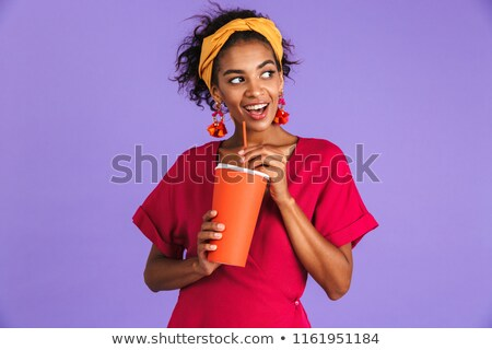 Cheerful african woman in dress drinking soda from paper cup Stock photo © deandrobot