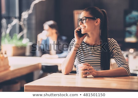 Young woman talking on mobile phone while enjoying a cup of coffee Stock photo © Kzenon