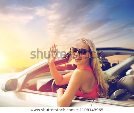 happy young woman in convertible car waving hand stock photo © dolgachov