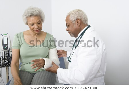 Doctor Checking Fractured Hand Of A Woman Stock photo © AndreyPopov