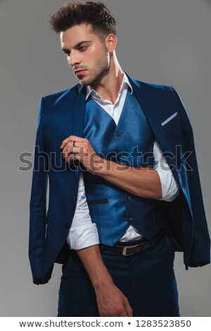 classy man holding suit collar while looking to side Stock photo © feedough