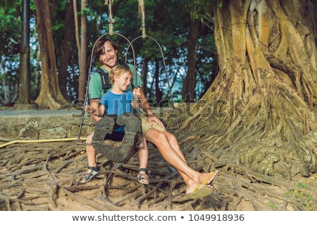 Dad and son swinging on an old swing against the background of the roots of the tree Stock photo © galitskaya