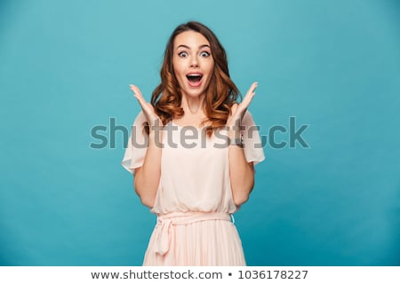 Shocked young woman posing isolated over blue wall background play games by mobile phone. Stock photo © deandrobot