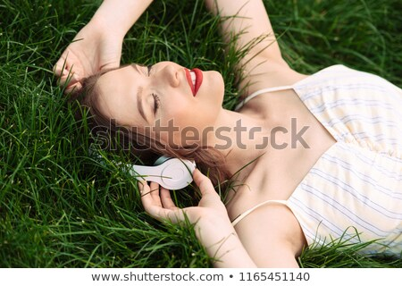 Pleased woman in dress and headphones lying on grass Stock photo © deandrobot