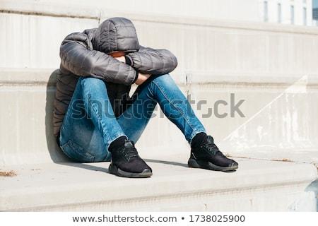 Férfi összegömbölyödve ül szabadtér lépcsőfeljáró fiatal Stock fotó © nito