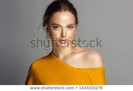 Makeup products. Young beautiful girl with gold earrings and ring smiling on white background. Red n Stock photo © serdechny