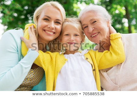 daughter with senior mother hugging on park bench stock photo © dolgachov