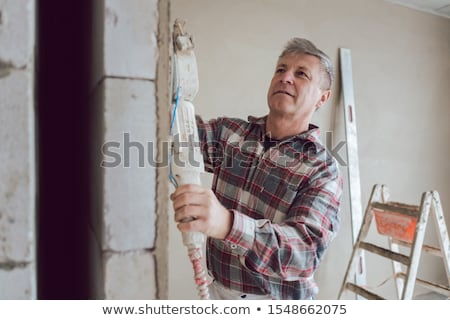 Plasterer smoothing interior wall of new homes with machine Stock photo © Kzenon