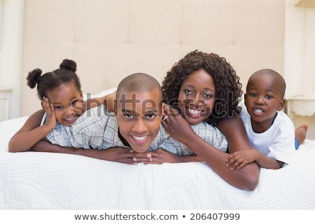 Front view of happy African American family relaxing on bed and looking at camera in a comfortable h Stock photo © wavebreak_media