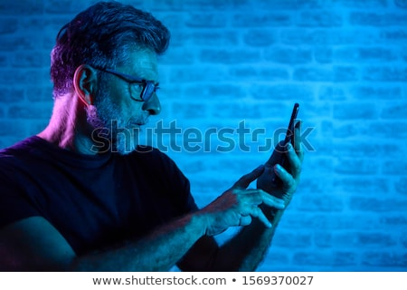 senior businessman using mobile phone against wall in office stock photo © boggy