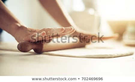 Baker hands preparing fresh dough with rolling pin on kitchen table Stock photo © Illia